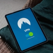 A tablet sits on a velvet cushion. The screen shows a VPN connection.